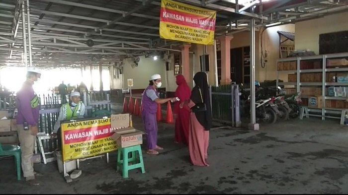 Peziarah diperiksa suhu tubuh sebelum memasuki kawasan Makam Guru Zuhdi di Banjarmasin.