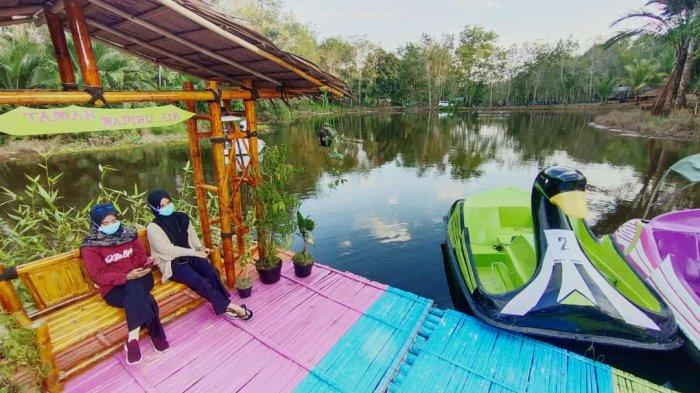 Wisata Kalsel, pengunjung objek wisata Taman Bambu Air  Desa Hauwai Kecamatan Halong Kabupaten Balangan, bersantai pada spot foto di tengah danau.