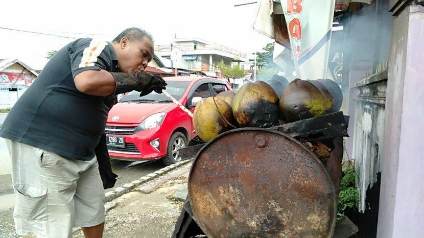 kuliner-kalsel-pak-iskandar-saat-membakar-kelapa-mudanya.jpg