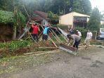 polisi-bersama-warga-saat-mengevakusi-pohon-tumbang-menimpa-r.jpg