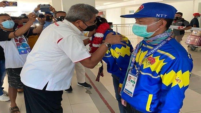 Sekretaris Umum KONI NTT mengalungkan selendang kepada Susanti saat penjemputan di Bandara El Tari Kupang, Rabu 6 Oktober 2021.