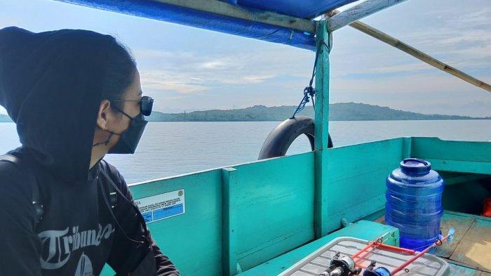 Seorang wisatawan lokal sedang memandang ke arah laut dari atas perahu motor