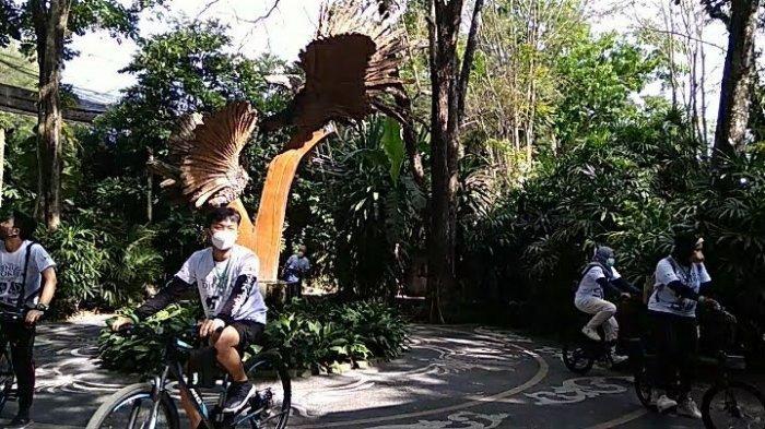 Bersepeda di bawah pepohonan yang rindang di Gembira Loka Zoo Jogya