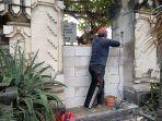 Seorang-pekerja-tengah-mengerjakan-pemasangan-batu-bata-di-akses-pintu-masuk-Pantai-Kuta.jpg