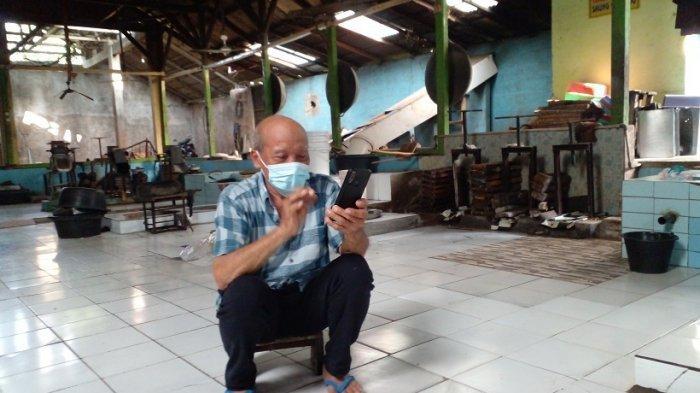 H Endut Rohadi melihat ponsel sementara pabrik galendo miliknya di  Jalan Kapten Harsono Sudiro, Cilame, Kabupaten Ciamis berhenti beroperasi