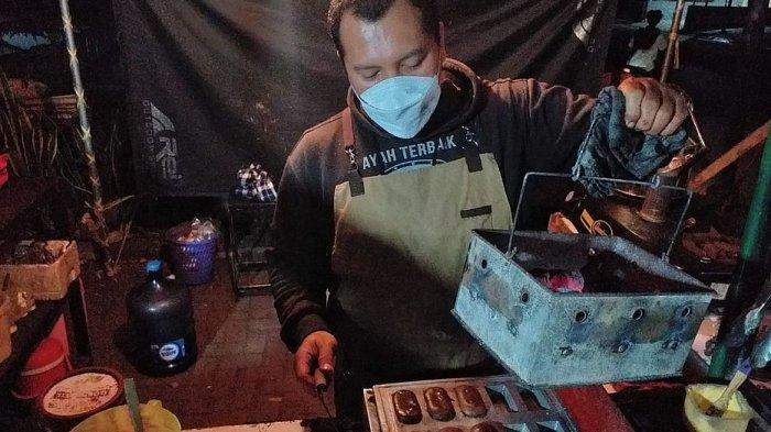 Ismail Edwin siap mengangkat kue balok dari adonan di jongkonya yang berada di halaman Kantor Desa Tanjungsari, Jalan Raya Bandung-Sumedang, Minggu (15/8/2021)