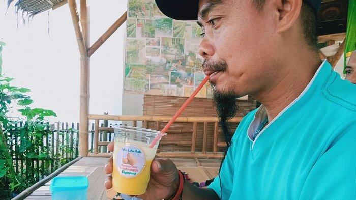 Seorang warga menikmati jus dari buah labu madu hasil olahan kelompok di Desa Ciganjeng, Kecamatan Padaherang, Kabupaten Pangandaran