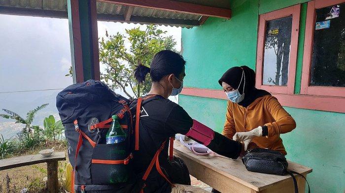 Seorang pendaki diperiksa tekanan darahnya sebelum melakukan pendakian ke Gunung Ciremai via Apuy, Majalengka, Sabtu (15/5/2021)