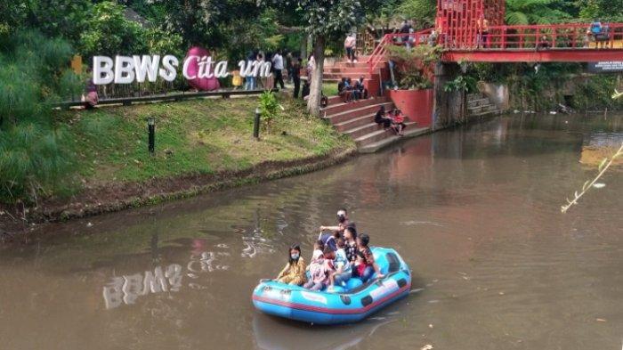 Pengunjung naik perahu karet menyusuri Sungai Cikapundung dalam jarak pendek di Teras Cikapundung, Babakan Siliwangi, Kota Bandung, Jumat (14/5/2021)