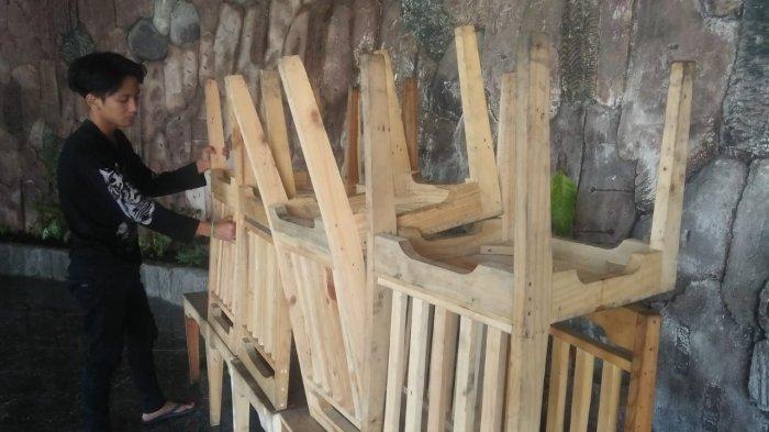 Gilang M Saurus mengerjakan  kursi dari kayu bekas limbah peti kemas di Desa Cikahuripan, Cimanggung, Sumedang
