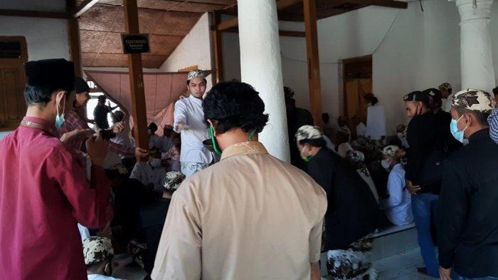 - Perwakilan keluarga Keraton Kanoman membagikan koin pada  tradisi surak yang menjadi rangkaian tradisi Grebeg Syawal di kompleks Makam Sunan Gunung Jati, Desa Astana, Kecamatan Gunungjati, Kabupaten Cirebon, Kamis (20/5/2021).