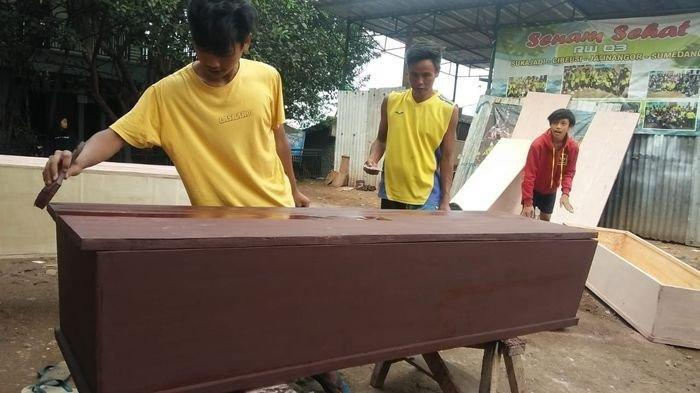 Proses pembuatan peti jenazah di Dusun Sukajadi RT 02/03, Desa Cibeusi, Kecamatan Jatinangor, Kabupaten Sumedang, Jawa Barat.