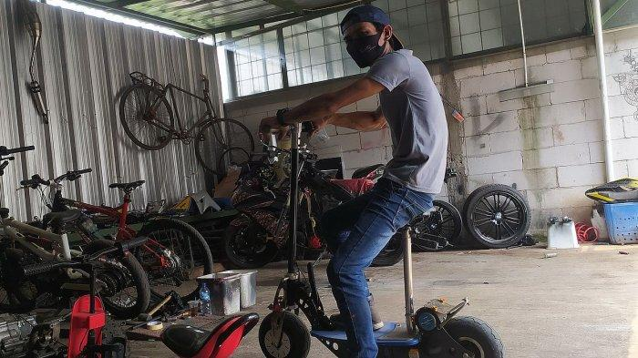 Rixy Julian Rahmat dengan sepeda motor listrik ciptaanya di bengkel DMR Custom Jalan Randusari Utara, Bandung