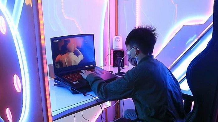 Pengguna Smart Box sedang menggunakan laptop di dalam boks cerdas yang kedap suara dengan lampu yang bisa diatur.