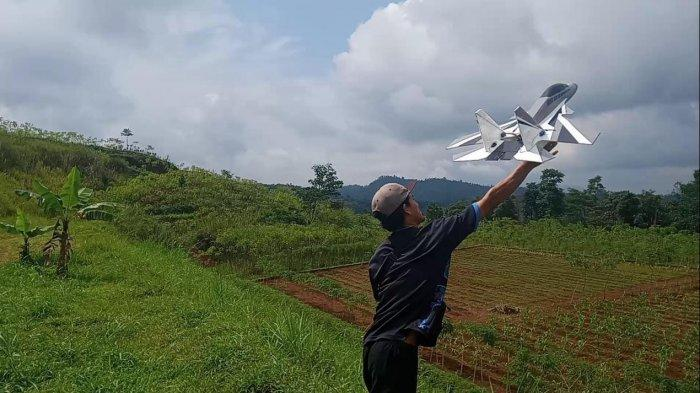 Wawan Ernawan menerbangkan pesawat aeromodeling buatannya di Sumedang