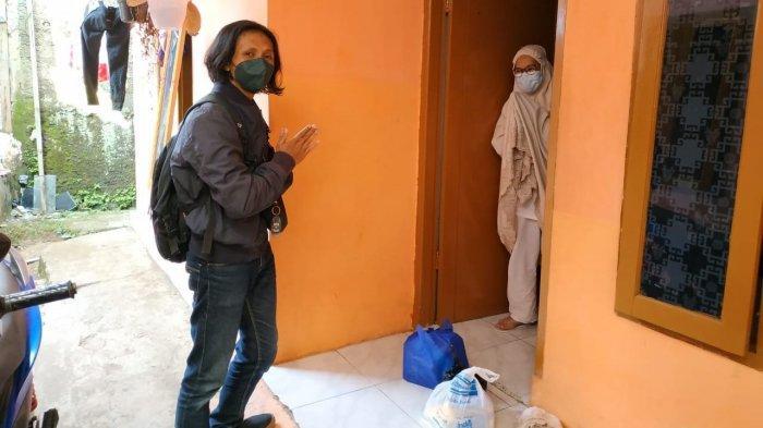 Wisnu Sopian (kiri) mengantarkan sendiri keperluan warga yang sedang menjalani isolasi mandiri di rumahnya.