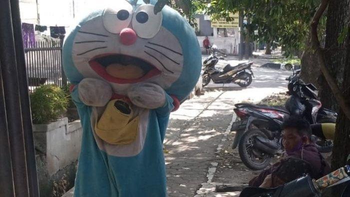 Pengamen boneka mengenakan karakter Doraemon di Kota Bandung