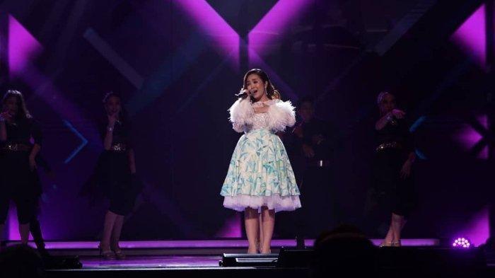 Dinda Permata sedang bernyanyi di suatu acara