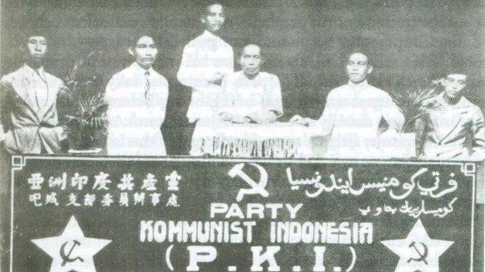 Para tokoh PKI sedang memegang bendera Partai Komunis Indonesia