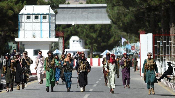 Pejuang Taliban berjalan di gerbang masuk utama bandara Kabul di Kabul pada 28 Agustus 2021, setelah pengambilalihan militer Afghanistan yang menakjubkan oleh Taliban.