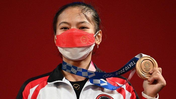 Peraih medali perunggu Windy Cantika Aisah dari Indonesia berdiri di podium untuk upacara kemenangan kompetisi angkat besi 49kg putri selama Olimpiade Tokyo 2020 di Tokyo International Forum di Tokyo pada 24 Juli 2021.