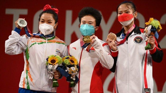 (Dari kiri ke kanan) Peraih medali perak dari India Chanu Saikhom Mirabai, peraih medali emas dari China Hou Zhihui dan peraih medali perunggu dari Indonesia Windy Cantika Aisah berdiri di podium untuk upacara kemenangan kompetisi angkat besi 49kg putri selama Olimpiade Tokyo 2020 di Tokyo International Forum pada 24 Juli 2021.