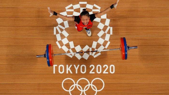Foto yang diambil dengan kamera robot ini menunjukkan reaksi Windy Cantika Aisah dari Indonesia saat berlaga dalam kompetisi angkat besi 49 kg putri pada Olimpiade Tokyo 2020 di Tokyo International Forum pada 24 Juli 2021.