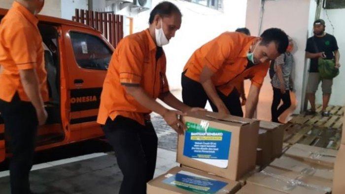 Petugas PT Pos Indonesia dan tukang ojek daring mempersiapkan paket sembako dari Provinsi Jawa Barat untuk disalurkan ke warga terdampak PSBB di Kota Bekasi, Rabu (15/4/2020). Bantuan bernilai Rp 500.000 per keluarga itu akan diantar langsung ke rumah warga.