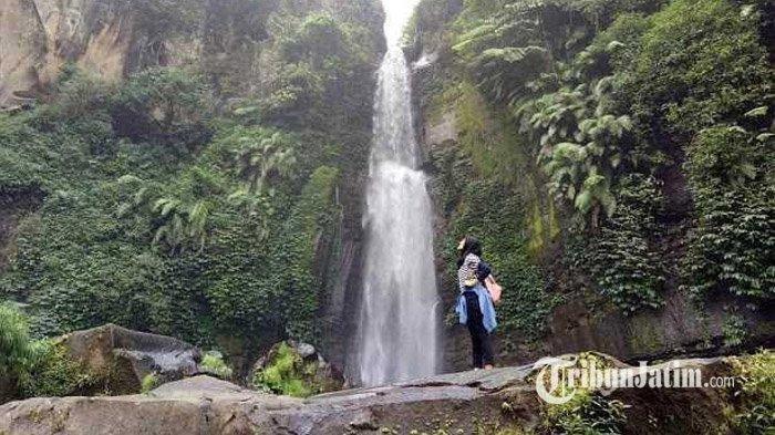 Seorang wisatawan sedang berfoto di bawah air terjun Coban Talun, Kota Batu