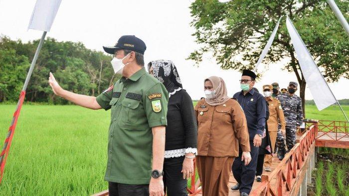 Gubernur Riau Syamsuar melambaikan tangan kepada warga saat berkunjung ke Desa Mentayan, Kabupaten Bengkalis, Senin (6/9/2021) sore