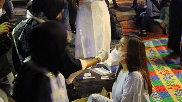 Petugas medis mengambil satu sampel swab test atau tes usap dari seorang pengunjung kuliner malam di Kota Pekanbaru, Minggu (23/5/2021)