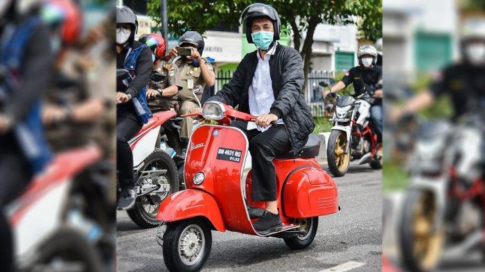 Walikota Dumai Paisan mengendarai vespa merah saat berkunjung ke rumah warga untuk membagikan sembako