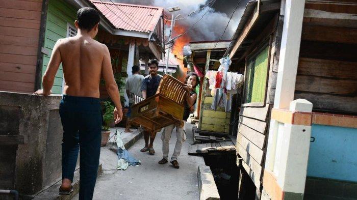 Warga terlihat mengevakuasi sejumlah barang saat terjadi kebakaran di Kawasan Kampung Wisata di Kota Dumai, Kamis (1/7/2021)
