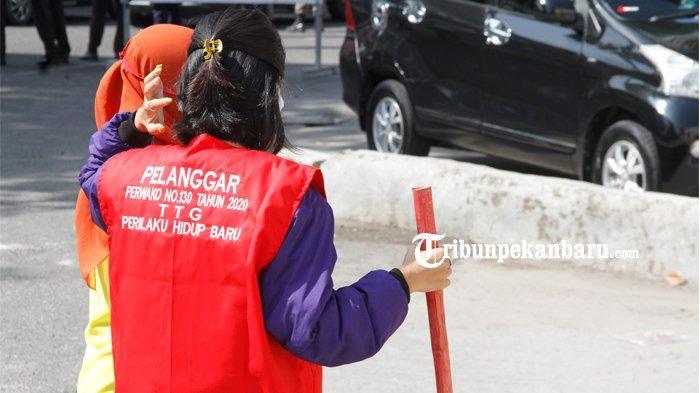 Warga terjaring razia masker mengenakan rompi khusus berwarna merah dengan tulisan pelanggar perwako nomor 130 tahun 2020 tentang prilaku hidup baru sedang menjalankan sanksi sosial, Senin (10/8/2020)