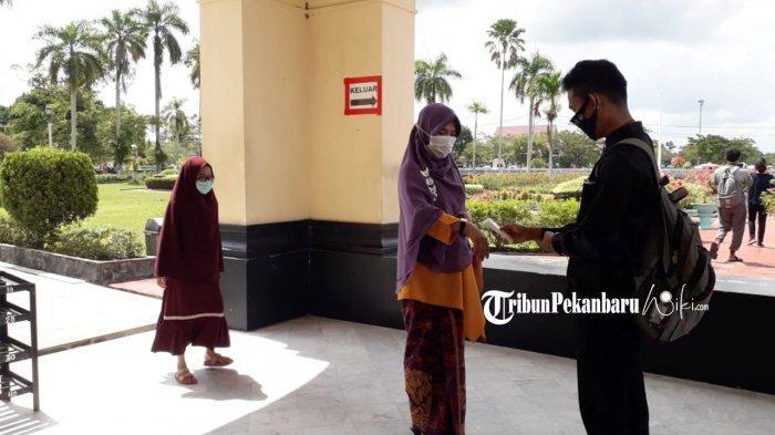 Pengunjung Istana Siak sedang dicek suhu tubuhnya sebelum masuk ke sitana oleh petugas.