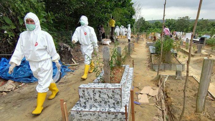 Petugas makam usai memakamkan pasien positif covid-19 yang meninggal dunia sesuai dengan protokol kesehatan di Pemakaman Kerinci Barat Kabupaten Pelalawan beberapa waktu lalu. (tribunpekanbaru.com/Johannes Wowor Tanjung)
