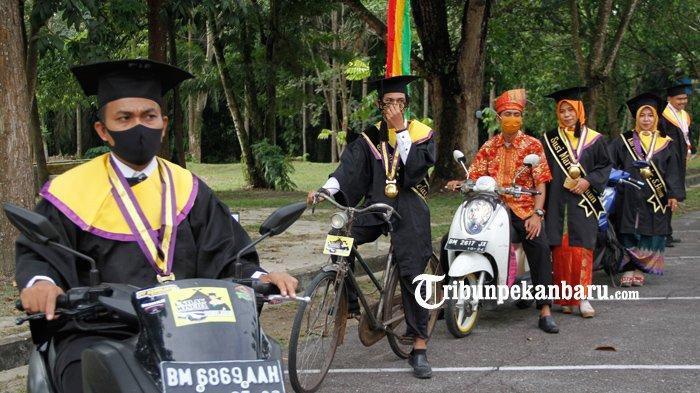 wisudawan naik sepeda ontel saat mengikuti wisuda ala drive thru di Universitas Lancang Kuning (Unilak), Rabu (5/8/2020)/ Doddy Vladimir