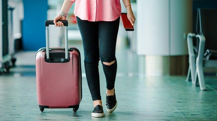Ilustrasi wisatawan membawa koper di bandara.
