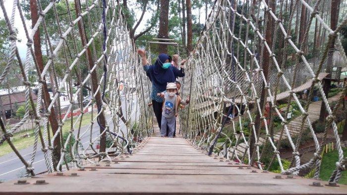 Pengunjung saat melewati jalan layang tali di The Lawu Park Tawangmenggu, Karanganyar, Sabtu (29/5/2021).